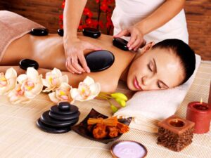 Adult woman having hot stone massage in spa salon.