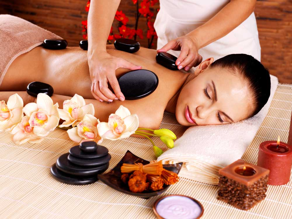 Adult woman having hot stone massage in spa salon.